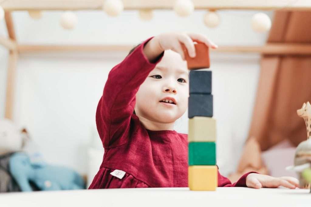 child playing wooden blocks
